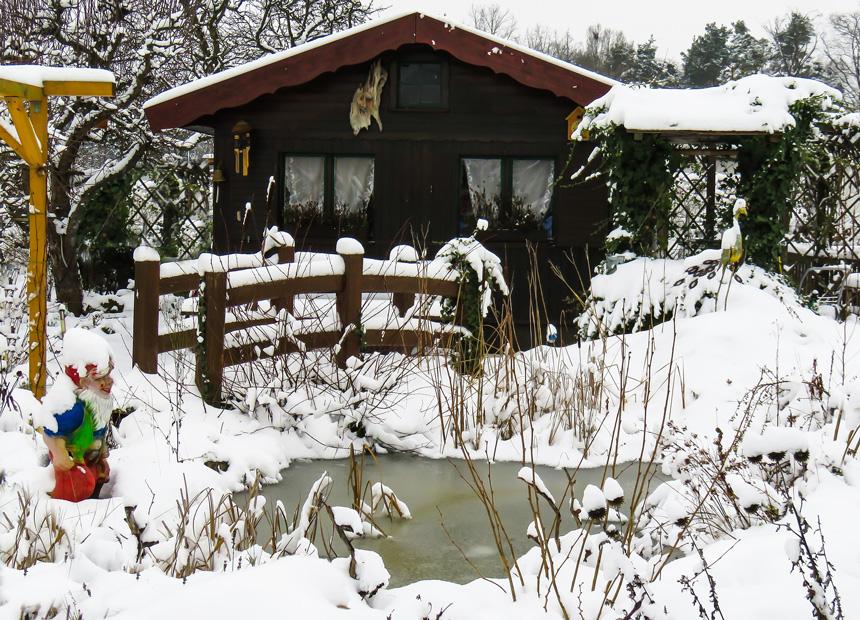 Befagyott kerti tó télen hiddal és házzal a háttérben